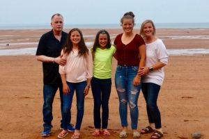 Ian McDonell pose en compagnie de ses trois filles et de sa femme à la plage.