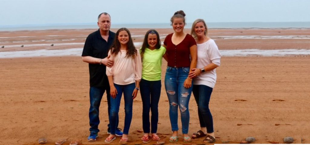 Ian McDonell, his three daughters and wife on the beach