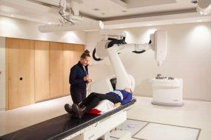 ulie Gratton en compagnie d'un patient près du robot CyberKnife