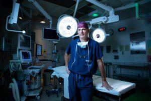 Le Dr John Sinclair prend appui sur la table d'opération.