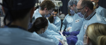 Hospital doctors and surgeons operating on a trauma patient