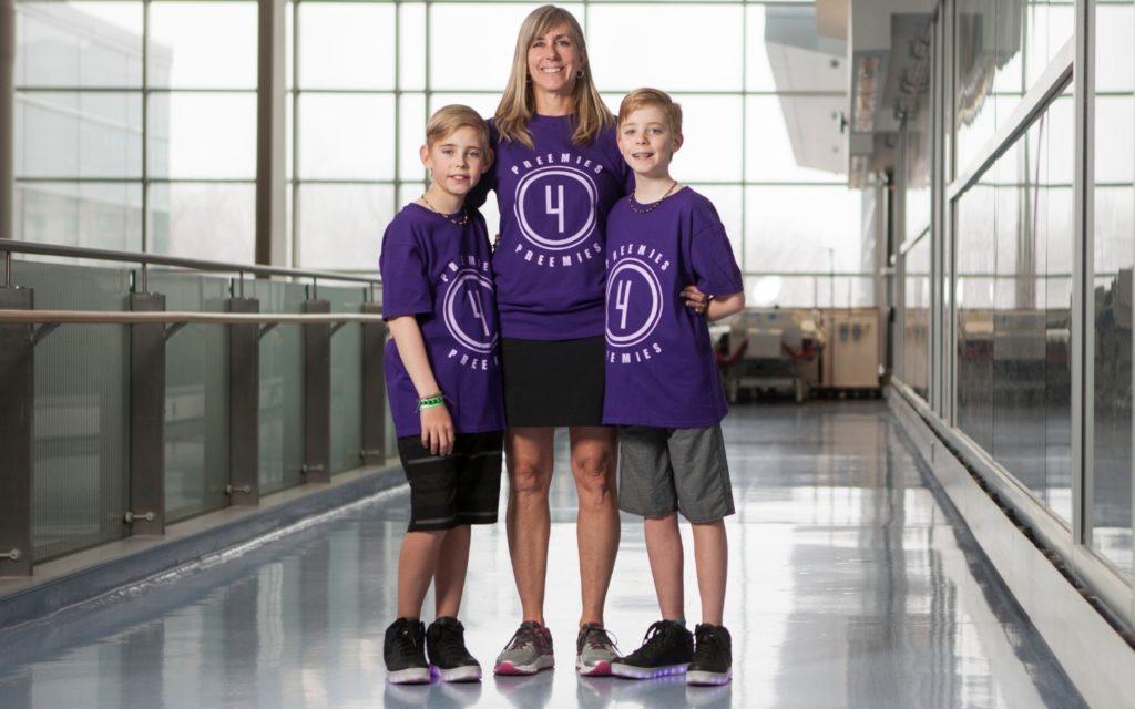 Nora, Liam, and Rhys Shipton smile wearing their Preemies for Preemies team shirts