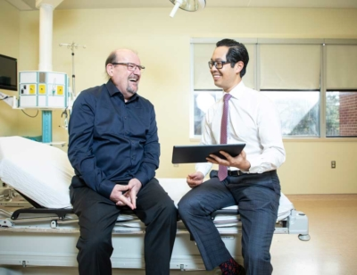 Dan Collins with Oncologist Dr. Michael Ong of The Ottawa Hospital in a patient room.