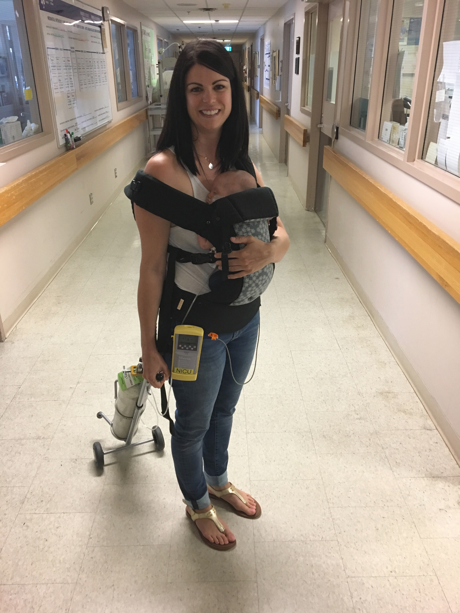 Jamie Eberts carrying baby Olivia and her oxygen tank