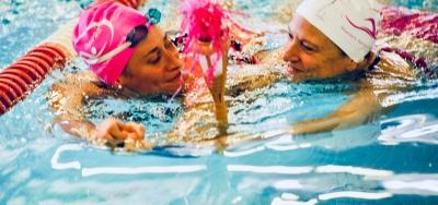 Andrea Smith, entraîneuse de natation porte la flamme olympique en compagnie d'une survivante du cancer du sein, Andrea Douglas.